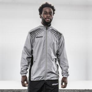 Model wears uhlsport Goal Presentation Jacket Dark Melange Grey Black